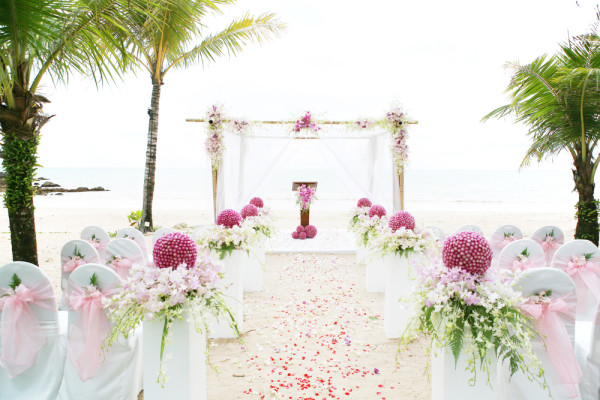 pink and purple wedding ceremony on the beach